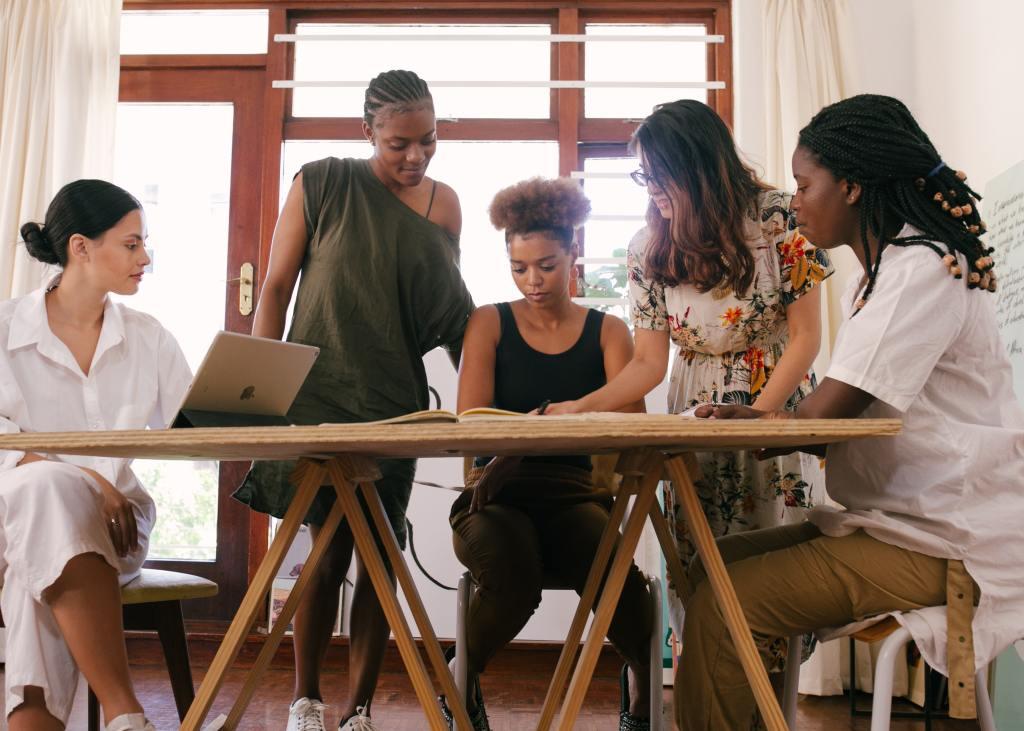 Mulheres reunidas em torno de uma mesa com computador e livro